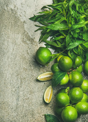 Flatlay of freshly picked organic limes and mint for making cocktail or lemonade over grey concrete stone background, top view, copy space, vertical composition