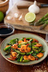 Salad with asparagus and shrimps in plate. Ingredients on the table