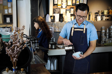 Portrait of barista making latte or cappucino coffee in coffee shop. Cafe restaurant service, food and drink industry concept.