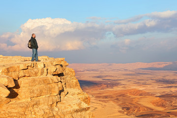Traveler (hiker man) on a mountain edge top. Colored sand stone desert under beautiful sky before sunset. Unique geological erosion land form. National park Makhtesh Ramon (Crater). Negev, Israel