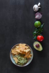 Plate of guacamole with tortilla chips and ingredients