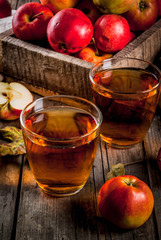 Fresh organic farm apple juice in glasses with raw whole and sliced red apples, on old rustic wooden table, copy space