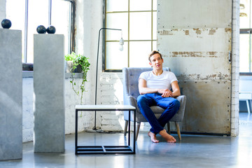 A young handsome man relaxing in a armchair in a loft style apar