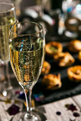 New Year: Glass Of Champagne With Party Food Behind