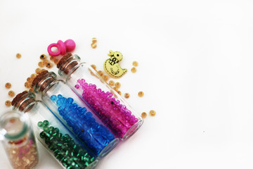 Tiny glass bottles filled with  colored  beads and elements for baby  spilling out, isolated on  white background with space for text.