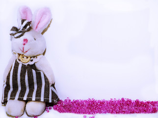 Cute baby frame or template with plush bunny and spilled rose beads. Space for text, invitation, greeting card.