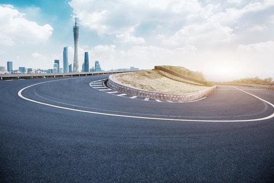 empty asphalt sharp turn with modern city