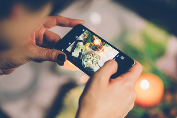 A young woman taking photo of food on smartphone, photographing meal with mobile camera