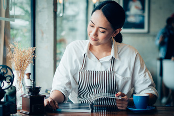 Asian business girl working and drinking coffee in cafe