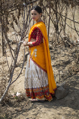 Full body Portrait of Indian woman wearing yellow rural clothes