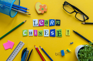 Word LEARN CHINESE made with carved letters on yellow desk with office or school supplies, stationery. Concept of chinese language courses