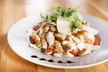Salad with chicken, mozzarella and cherry tomatoes. Caesar salad served at a restaurant.