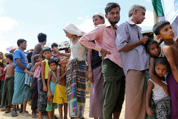 Rohingya refugees gather in front of a temporary healthcare center to get an oral cholera vaccine, distributed by WHO, in the Jamtoli refugee camp in Cox's Bazar
