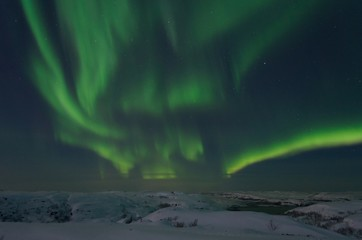 Northern lights in winter over snowy hills.