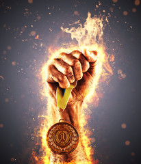 Man's hand in a fire is holding up gold medal. Winner in a competition.