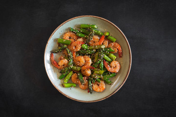 Salad with asparagus and shrimps in plate. Central composition