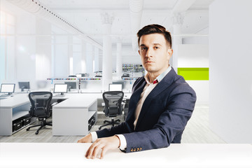 Attractive businessman with modern suit sitting against modern office view