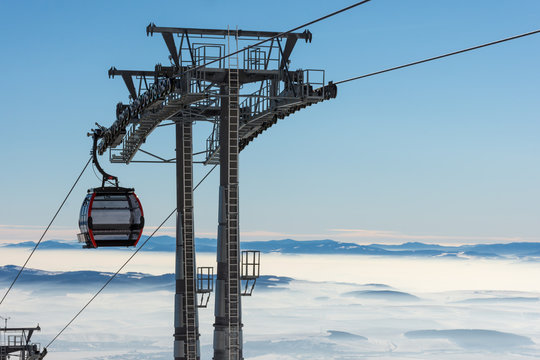 Gondola lift. Cabin of ski-lift in the ski resort in the early morning at dawn with mountain peak in the distance. Winter snowboard and skiing concept