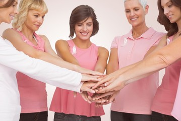 Composite image of female friends stacking hands for breast