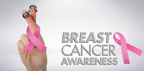 Composite image of cropped hand holding breast cancer awareness