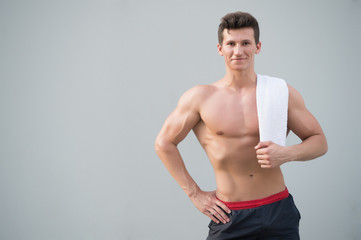 Sportsman smiling with towel on grey background