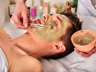 Mud facial mask of man in spa salon. Massage with clay full face. Girl on with therapy room....