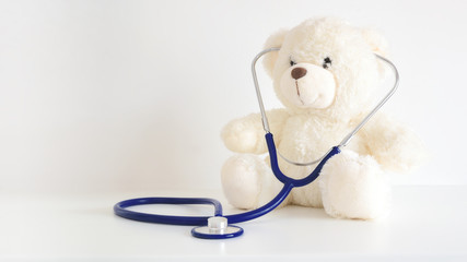 Teddy bear with a stethoscope. Pediatrician healthcare for children. Empty copy space for Editor's text.