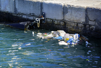 Beach pollution. Plastic bottles and other trash on sea port