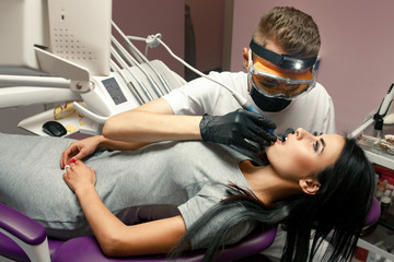 Young woman treats teeth in dental office. Male dentist treats her teeth with dental drill.