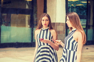Young Beautiful Woman standing by metal mirror on street, holding cell phone, looking at reflections, texting, thinking. Concept of self assured, self esteem, self checking. Filtered effect..