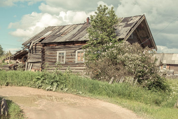 north Russian village Isady. Summer day, Emca river, old cottages on the shore, old wooden bridge. Abandoned building.
