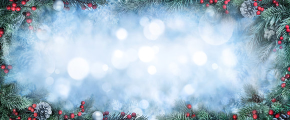Christmas Background with frosty fir branches as a frame around blue bokeh copy space