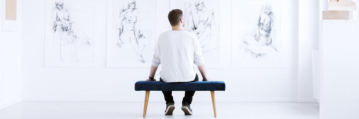 Man looking at charcoal drawings