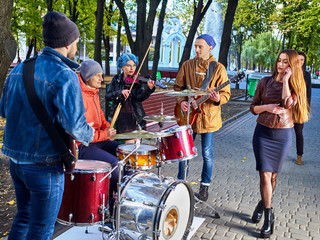 Festival music band. Friends playing on percussion instruments in city park. Fountain and trees in the background. People earn money to live.