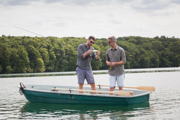 Two caucasian men are preparing their equipment for fly fishing from a boat on lake.