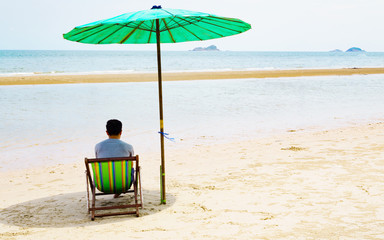 lonely man sitting and thinking on the beach. Summer vacation in Thailand beach.