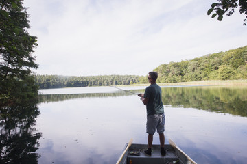 A man is fly fishing from a boat on a lake.