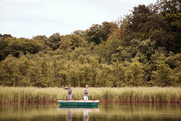 Two caucasian men are fly fishing in boat on lake.