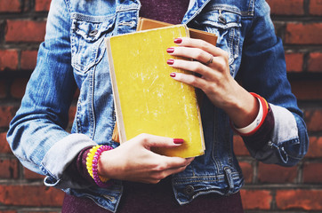 Hipster student girl with bracelet and red nails holding books in her hands