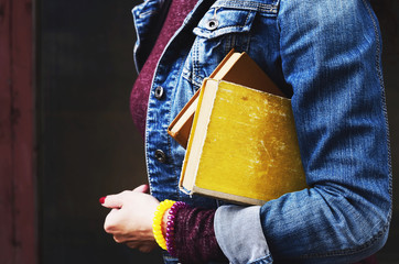 Young woman in jeans jacket holding pile of books in her hand