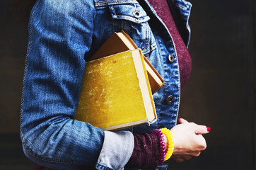 Young woman in jeans wear holding old books in her hand