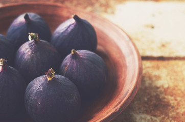 Ripe figs in clay bowl on grunge metal background