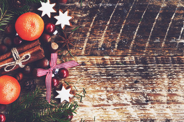 Xmas decoration with tangerines, spices, gingerbread cookies with copy space on wooden background