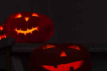 Scary Halloween pumpkins. Scary glowing faces trick or treat. Focus on the front pumpkin