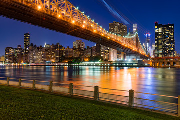 Evening view of Manhattan Midtown East from Roosevelt Island with the illuminated Ed Koch Queensboro Bridge and the East River. New York City
