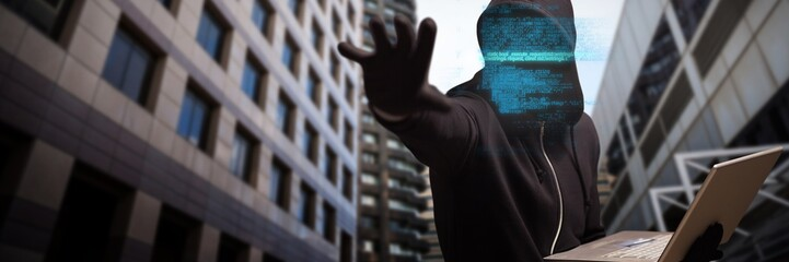 Composite image of hacker holding laptop while gesturing
