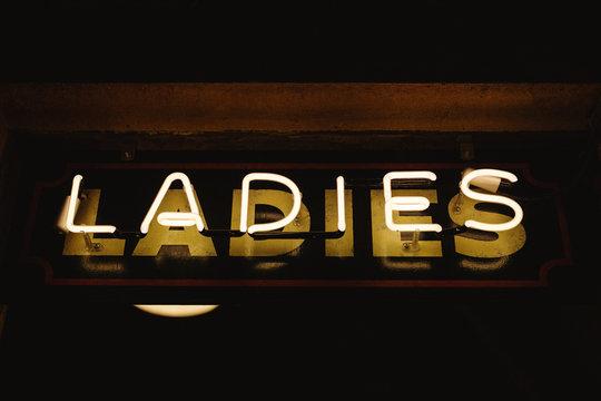 Neon sign: ladies restroom.