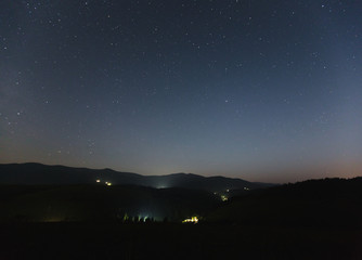 Starry sky over the mountains and mountain village.