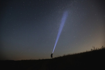 The man point flashlight to the night sky.