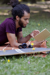 african man reading a book in park